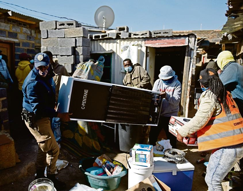Members of the police and other law enforcement agencies confiscate a fridge and other items that were stolen during the looting spree in Alexandra last week. Photo: Tebogo Letsie/City Press