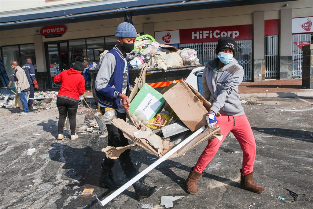 Residents clean up in the aftermath of the looting spree at Jabulani Mall in Soweto. Photo: Sharon Seretlo/Gallo Images