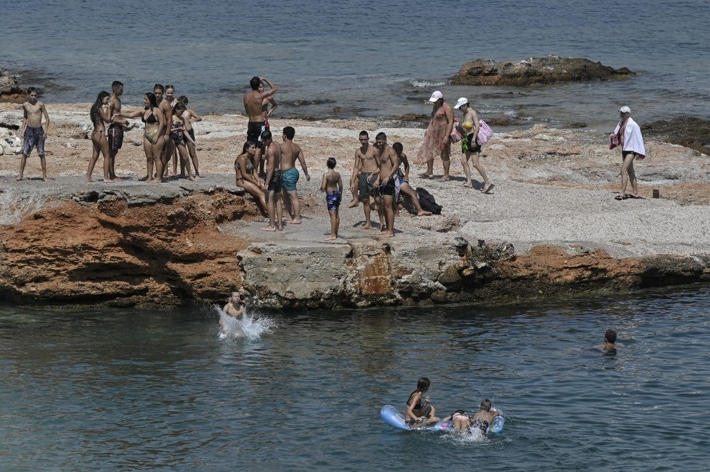 Youth enjoy the waters at Varkiza near Athens as Greece faces a week-long heatwave.