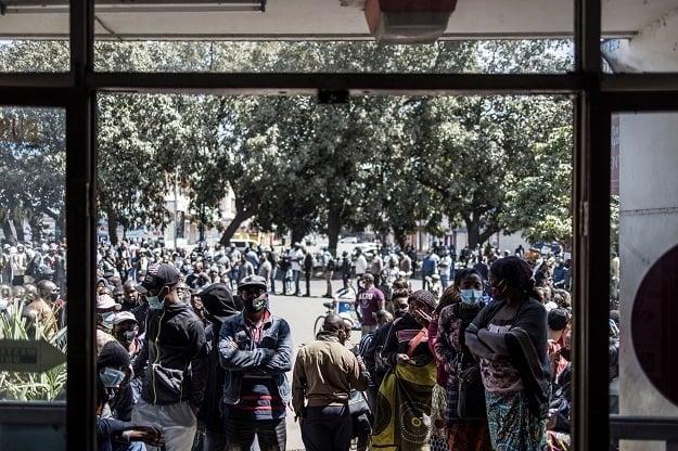 En esta vista a través de la ventana, los votantes se muestran esperando un