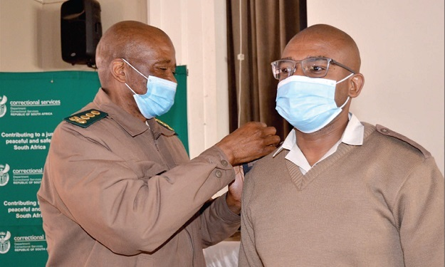 Samuel Makgothi Thobakgale (right) gets pinned with rank insignia.