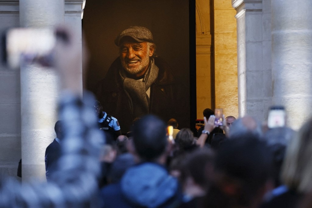 People wait to pay their respects to late French actor Jean-Paul Belmondo as they stand in front of his casket after the national tribute ceremony at the Hotel des Invalides in Paris, on September 9, 2021. (AFP/Thomas Samson)