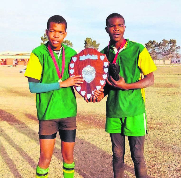 Ubumbo Sport Academy players, from left, Flanker Someleze Gantsho and two-try hero in the final, Siyavuya August, with the Edwin 'Nutse' Ngculu Cup, at Mlungisi Stadium in Komani.                 Photo: THANDO MGEDEZI