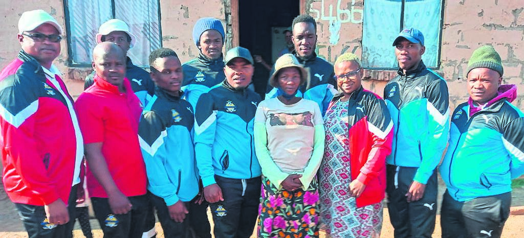 Members of the Endaweni Football Club with one of the families who benefitted from the donation.                                               Photo:SUPPLIED