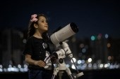 Brazilian 8-year-old astronomer Nicole Oliveira poses for a picture with her telescope in Fortaleza, Brazil, on September 21, 2021. When Nicole Oliveira began to take her first steps, she raised her arms to the sky, trying to catch the stars. Now, only eight years old, she is a young Brazilian astronomer who hunts asteroids. (JARBAS OLIVEIRA / AFP)