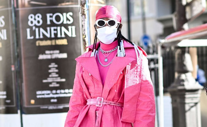 A guest is seen wearing a pink coat, pink checkered pants and pink do-rag outside the Raf Simons show during Paris Fashion Week S/S 2022 on September 30, 2021 in Paris, France. Photo by Daniel Zuchnik/Getty Images