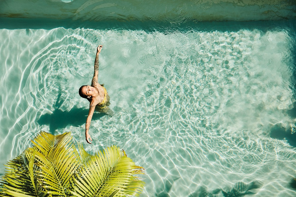 Overhead view of woman relaxing in pool at outdoor