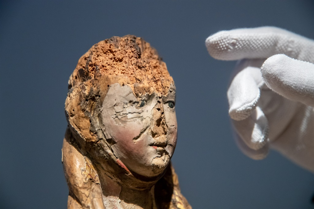 """Oliver Mack, head of the Institute for Art Technology and Conservation at the Germanisches Nationalmuseum and chief restorer, points to the damage caused by woodworm to a sculpture of the """"Holy Virgin"""". Art treasures in the museum are a found food for insects. (Photo by Daniel Karmann/picture alliance via Getty Images)"""