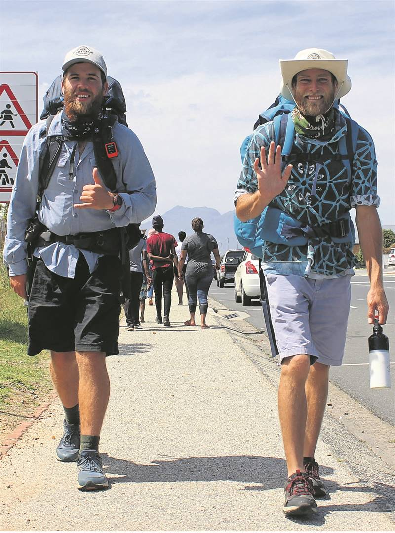 """Damian Honeysett and Damien Laird from KwaZulu-Natal are walking the South African Coastline, all the way from Mozambique to Namibia. The duo recently walked through Hermanus, Kleinmond and Betty's Bay. In this photo they stopped at the Natural Health Coffee Shop for some smoothies. On 8 October they travelled from Betty's Bay to Cape Town via Clarence Drive. When asked how they managed to walk this far they smile and say """"we take it one step at a time."""" Photo: Rick Marais"""