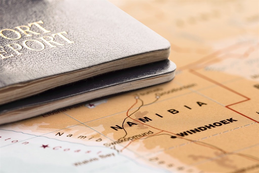 Two passports on the map of Namibia, are ready for travel.