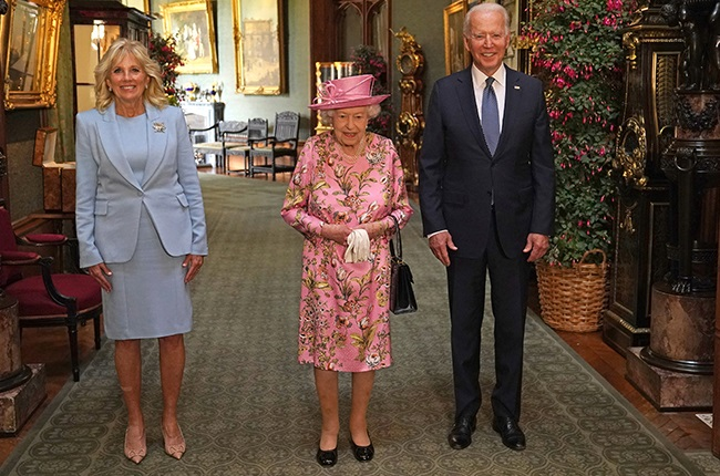 US President Joe Biden (R) and US First Lady Jill Biden (L) pose for a photograph with Britain's Queen Elizabeth II (C) in the Grand Corridor at Windsor Castle in Windsor.