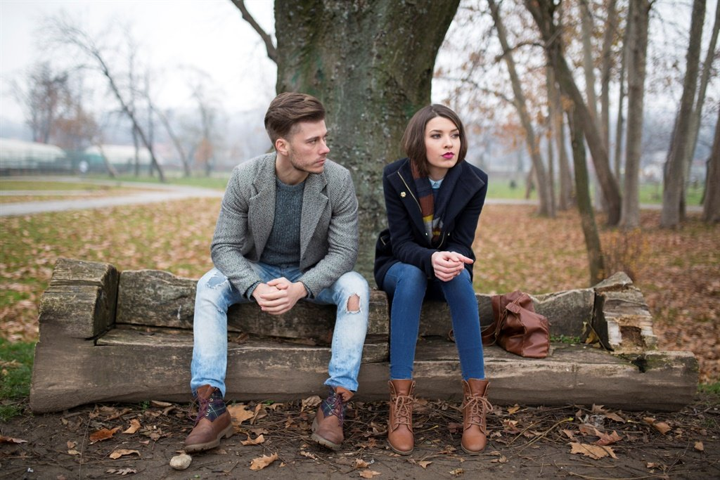Young couple sitting on the bench in the park, hav