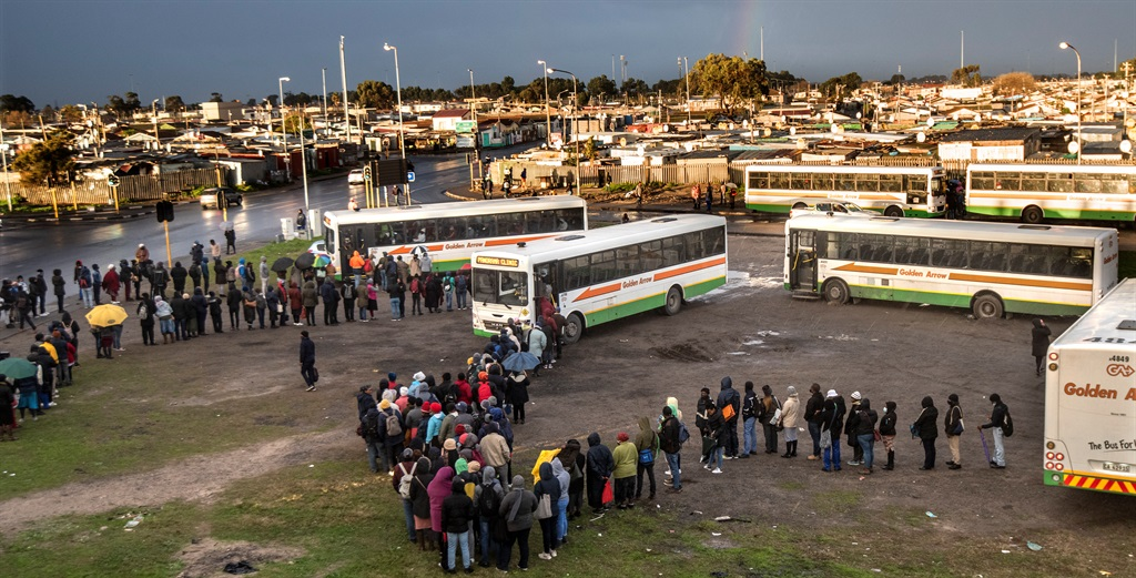 Golden Arrow buses stopped alongside the N2 to transport workers who stood in long lines in the pouring rain amid ongoing taxi violence. (Photo by Gallo Images/Brenton Geach)