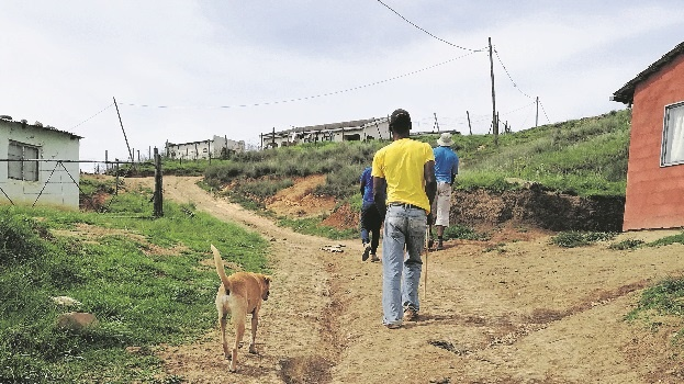 Ernest Mdunge, who is blind, uses only his knowledge of the footpath and his dog Mango to guide him on the bumpy dirt road to fetch water.