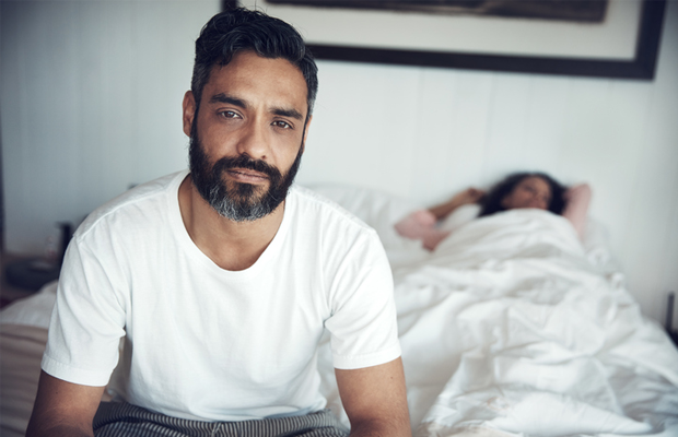 Man looking unhappy sitting on bed