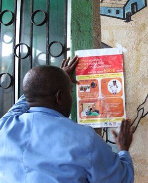 A nurse sets an information sign about Ebola on a wall of a public health center. (Stringer, AFP)