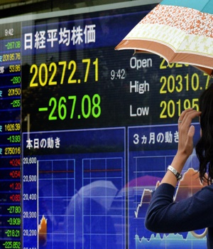 A woman looks at a share prices board in Tokyo, as
