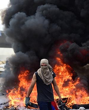 A Venezuelan opposition activist is pictured next to a burning barricade during a demonstration against President Nicolas Maduro in Caracas. (Ronaldo Schemidt, AFP)