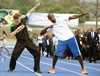 Britain's Prince Harry follows the signature victory gesture of Olympic sprint champion Usain Bolt after the two raced each other. (John Stillwell, AP)