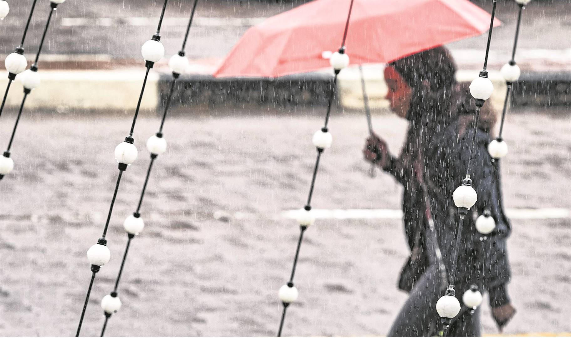A file image of a woman with umbrella walking in the rain.
