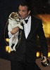 Uggie gets a kiss and a cuddle from Jean Dujardin, who plays his owner and silent film co-star in The Artist.