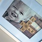 """I love you"" spelled out with scrabble tiles on a photo frame. So cute!"