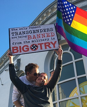 Nick Rondoletto, left, and Doug Thorogood, a couple from San Francisco, wave a rainbow flag and hold a sign against a proposed ban of transgendered people in the military at a protest in the Castro District. (AP)