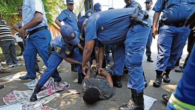 One protestor being handcuffed by police as he resisted arrest by lying on the floor of the Doull Road municipal depot.