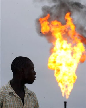 A Nigerian youth looks at smoke from gas flare belonging to an oil company in Ebocha, Nigeria. (AP)