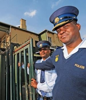 Pietermaritzburg police spokesperson Mthokozisi Ngobese (left) and Pietermaritzburg Cluster Commander Major-General Lucas Ngobeni shut the gates on one of the alleged illegal brothels operating in the city yesterday.