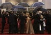 Isabelle Huppert holds hands with director Michael Haneke as they walk the rain-drenched red carpet for the screening of Palme d'Or winner Love. Strong winds and rain damaged the roof of a Cannes screening room and soaked stars were left shivering on