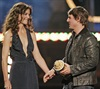 Their headline-grabbing romance was a promotional goldmine. In June 2005, Katie was on hand to present Tom with the first MTV Generation award at the MTV Movie Awards.