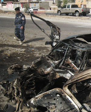 An Iraqi police man inspects the scene of a car bomb attack. Picture: Emad Matti/AP