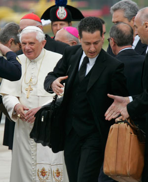 Pope Benedict XVI's butler Paolo Gabriele, right, carries the pontiff's bags as they arrive at Ciampino military airport in Rome. (File, AP)