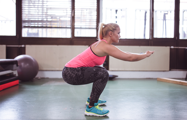 Woman doing a squat in the gym