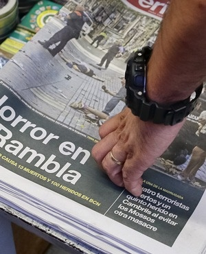 A man touches a newspaper displaying a photograph of the aftermath of the terror attack in Las Ramblas, Barcelona. (Manu Fernandez, AP)