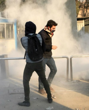 Iranian students run for cover from teargas at the University of Tehran during a demonstration driven by anger over economic problems. (STR/AFP)
