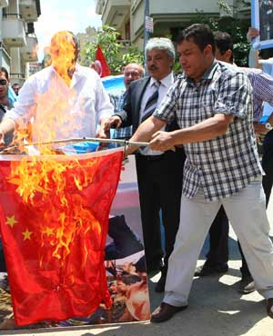 Uighurs living in Turkey set a Chinese flag on fire as they stage a demonstration outside the Chinese embassy in Ankara. (Adem Altan, AFP)