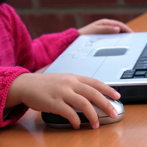 child's hand on computer mouse