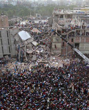 Bangladeshis watch the rescue operations at the site of a building that collapsed in Savar, near Dhaka, Bangladesh. (Kevin Frayer, AP)