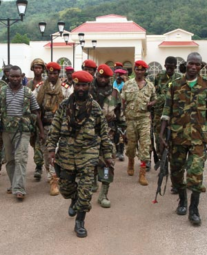 Rebel soldiers from the Seleka alliance walk in front of the Ledger Plaza Bangui hotel, in Bangui, Central African Republic. (AP Photo)