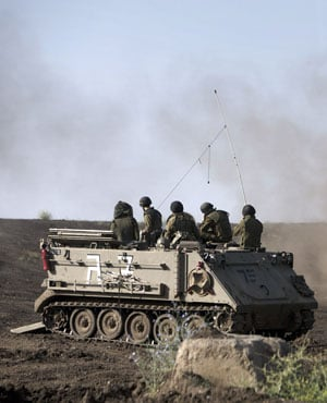 An Israeli Armoured Personnel Carrier (APC) and Merkava tanks. (Menahem Kahana, AFP)