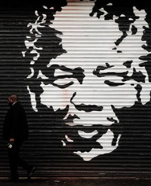 A man walks past street art depicting former president Nelson Mandela in Woodstock, Cape Town. (Nardus Engelbrecht, Sapa)