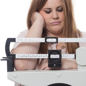 Woman on scale struggling to lose weight