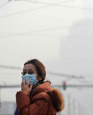 A woman wearing a face mask makes her way along a street in Beijing. (Wang Zhao, AFP)