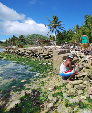 Inhabitants of Kiritimati coral atoll building a stone seawall to struggle against sea level rise caused by global warming. (AFP)