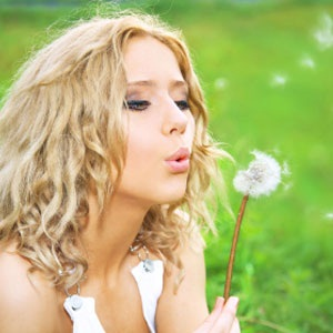 Woman with hay fever blowing flower