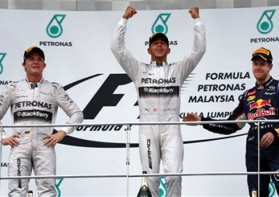 <b>FIRST WIN AT SEPANG:</b> Mercedes' Lewis Hamilton (centre), celebrates on the podium after winning the 2014 Malaysian GP. Team mate Nico Rosberg (left) finished second ahead of Red Bull Sebastian Vettel. <i>Image: AP</i>