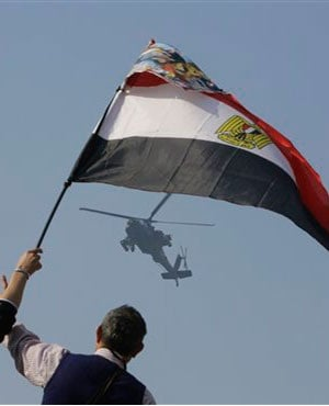 Egyptians wave a national flag as they greet an army helicopter. (Amr Nabil, AP, file)