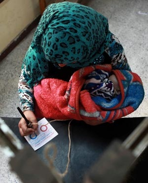 An Egyptian woman holds a child as she casts her vote in the country's constitutional referendum in Hawamdaya, 40km south of Cairo, Egypt. (AP)